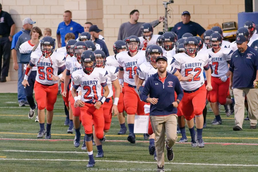 The football team, leaded by their coach, runs out before the game begins.