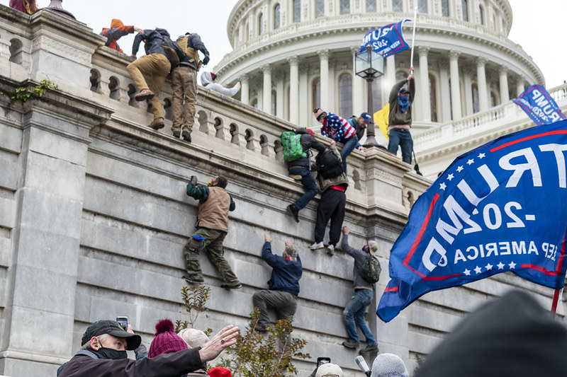 Rioters scaling a wall on Capitol Hill.