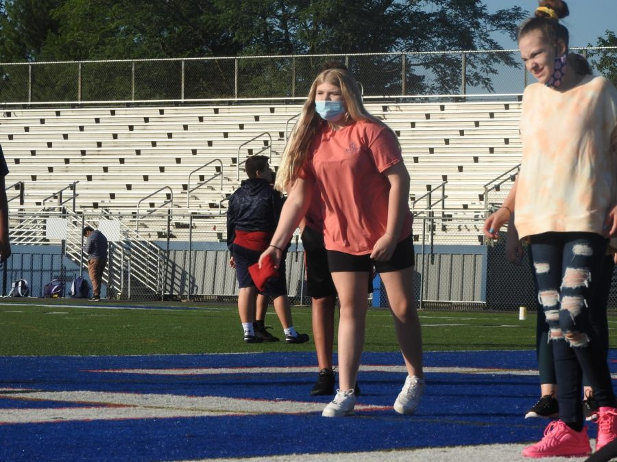 Carly McDonough tosses her beanbag while participating in the cornhole competition.
